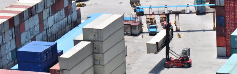 Trucks carrying freight containers through customs gate